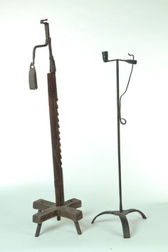 "FLOOR STANDING LIGHTING DEVICES.  American, 19th century. Pine trammel base with wrought iron rush light holder and weight, 43""h., and wrought iron rush light and candle holder, 34""h."