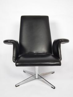 Beautiful 60s chair with 'wing shaped' armrests and a chrome swivel base: a real mid century  beauty. The chair is upholstered in black leatherette.