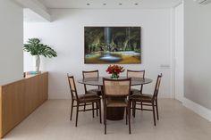 Decoração de apartamento com cores neutras, na sala de jantar mesa de madeira redonda, cadeiras de madeira e quadro.