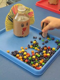 """I came up with this idea on a whim when thinking of a way to get my preschoolers to move items one at a time with tongs or tweezers.  I decorated a small water bottle to look like a turkey and gave them beads and a strawberry picker.  Just challenging enough for them to pick up and """"FEED THE TURKEY.""""  I think I will do the same with Santa and have the kids feed him """"Cookies."""""""