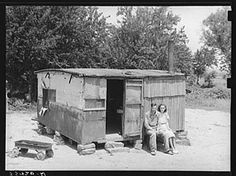 "Worker and his wife in front of their shack home on the Arkansas River near Webbers Falls, Oklahoma. This man said that last year he thought maybe he would be a little better off when he got the WPA work and had a small amount of cash coming in, but that he was worse off now. 'Last year I had a cow and some chickens and I had to sell my cow and eat my chickens. I get worse off every year'"" (Russell Lee, 1939)"