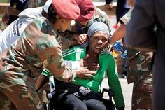 Collapse: Soldiers assist a woman who collapsed after bidding farewell to former president Nelson Mandela lying in state at the Union Buildings in Pretoria. (AFP)