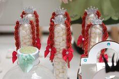 """Tubetes com confeitos de chocolate enfeitavam a mesa principal dessa festa com tema """"Frozen"""". Os frascos eram decorados com tranças ruivas, uma alusão ao cabelo da princesa Ana, personagem da animação"""