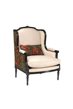 The Bergère à Oreilles is shown in Cherry wood with an Antique Black finish. This Louis XVI armchair features delicate hand-carved details and a loose seat cushion.
