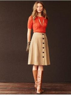 Approved.  Cable-knit sweater tucked into an a-line skirt with boots - not for everyone but she's pulling it off!