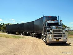 This looks like a purpose built three trailer road train. Note that the third trailer is longer than the other two.
