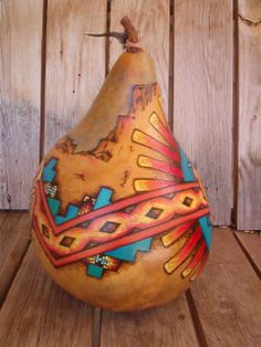 """""""Kokopelli & the Spiral"""" (back view) Original gourd design by Lani Walton. Large uncut gourd extensively wood burned & then painted in acrylic paints & water color pencil for blending colors. Some faux paint beading has been incorporated. Embellished with feather & wood beads on a a leather thong."""