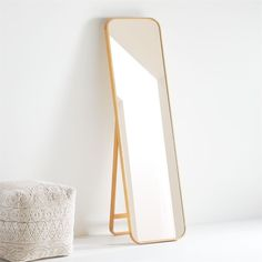 Edged with a slim band of solid oak, this minimalist standing mirror curves a rounded rectangle of modern elegance. The freestanding mirror, a Crate and Barrel exclusive, leans on a stand that echoes the curves of its frame. With its honey-hued wood border, the slim standing mirror is an understated essential. Group with our Edge round, capsule, and rounded rectangle floor and wall mirrors in brass, silver, black and walnut to create an intriguing geometric display.    Oak, mirrored glass and en