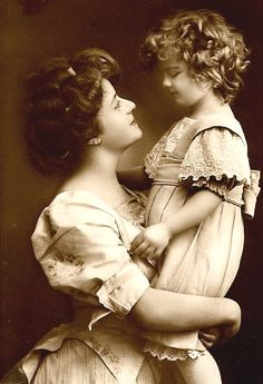 Antique photo from around 1900 of a doting mother and child dressed in their spring finery. (Photographer unknown.)