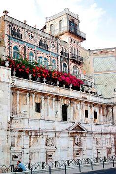 Foto: Chafariz D'El Rei e Palacete do Chafariz D'El Rei [ou Palacete das Ratas] – Lisboa, (Portugal).  O Chafariz de El-Rei, que terá sido o primeiro chafariz público na cidade de Lisboa, terá sido construído no século XIII, nos reinados de D. Afonso III de D. Dinis, aproveitando as excelentes águas da encosta de Alfama. O encanamento de água da nascente para bicas exteriores à chamada Cerca Moura datará de 1487, permitindo o abastecimento dos navios da carreira da Índia. A actual fachada…
