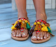 """Handmade sandals made of genuine leather. Very comfy and steady, consisting of two leather straps on the front of the foot and one more in the back. We sew the straps by hand with fringes, fabric and metallic trims and pom poms. """"Afrika"""" are embellished with gold plated charms that portray the tree of life and with small wooden lions.  The colors, motifs and the style influence of the sandals come from the unique and wild African continent. From the tropical forests to the endless rippling…"""