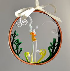 A quilled paper Christmas ornament, a candle with holly and curling smoke. Whomsoever