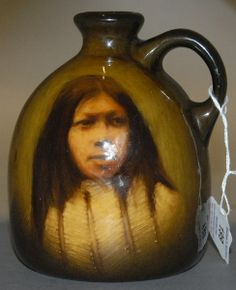 Rookwood pottery jug featuring a young Indian Brave with porcupine breast shield, signed S.M. probably Sadie Markland 1892-1899 Commache, marked on bottom SMI Rookwood 747C. ht. 5 7/8in.
