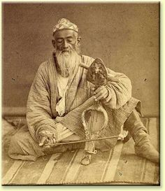 """A musician in Samarkand playing what is described as a """"kauz"""", apparently related to a violin of sorts. Hs is seated on a striped kilim, possibly Uzbek, dressed in leather boots and a simple robe composed of a striped fabric. Note the embroidered hat on his head, apparently exhibiting an abstract geometric design."""