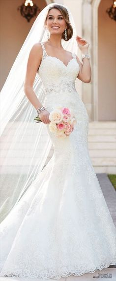 This embroidered lace fit and flare wedding dress from Stella York features regal Diamante beading that is heavily focused at the waist. The elegant lace shoulder straps showcase the face, while the back boasts a sexy band of sheer lace and an easy-to-close- zipper covered by fabric buttons.