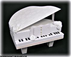 """Elke's 3D """"White Wedding Piano"""" is so gorgeous!  She used white cardstock to build the piano and the panels are cut out of velvet-covered cardstock!  Ribbon, roses, pearls!  I bet it is even prettier in person!  The 3D Grand Piano is from the THANK YOU FOR THE MUSIC SVG KIT!   Stunning!"""