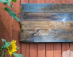 Welcome you and your guests home with this graphic hand painted pallet art, featuring a single Dandelion Seed hand painted over a blue color wash on wood pallet boards, with the phrase Make A Wish painted in the bottom left corner. This rustic pallet art measures approximately 30 x 16, is hung by very heavyweight picture hanging wire screwed into the back. Features an original dandelion seed painting and carefully hand lettered by me. Made from recycled pallet board and gives a pop of color…