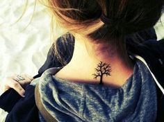 Chica sentada de espaldas sobre una cama mostrando el tatuaje que tiene en forma de árbol que esta en su cuello