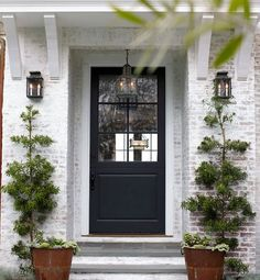 Love the style and color of the front door, the lanterns, brackets and those crazy-in-a-good-way evergreens.  I also super love whitewashed brick!