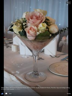 Short martini glasses filled with same flowers as my bouquet for top table