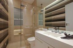 """O arquiteto Ricardo Rossi idealizou o banheiro com quatro metros quadrados de modo a torná-lo funcional e agradável: as faixas horizontais de porcelanato e o grande espelho que revestem as paredes dão a sensação de amplitude ao local. A bancada com cuba esculpida, o pano de vidro fixo no boxe e o nicho para xampu também aproveitam a área. Para reproduzir em casa, a dica do arquiteto é """"setorize cada uma das funções, assim você organiza e economiza espaço"""""""