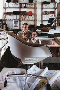 Portrait of married American designers Charles (1907 - 1978) (left) and Ray Eames (1912 - 1988) as they pose behind one of their chairs, which sits on a table in their studio, Venice, California, November 16, 1974. This photo was taken as part of a shoot for Fortune Magazine.