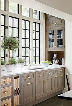 taupe kitchen with creay shades and brass handles looks chic