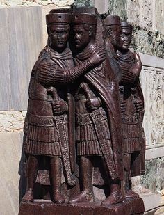 """The Tetrarchs, AD 305. Porphyry. This portrait of the tetrarchs was probably originally part of the palace in Constantinople, but is now built into the corner of St. Mark's Basilica in Venice. The style here reflects a new emphasis on the position of Emperor, rather than the person holding this office through """"similitudo"""": a generic face that is not particularly accurate to the individual, but emphasizes the similarity among the four tetrarchs."""
