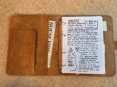 John Winchesters Journal from the TV show Supernatural. This journal is as close to a perfect replica as can be made. The journal is made from a faux leather material in a light brown colour and has three pockets. The ring binder mechanism has four rings. The journal can be purchased either by itself, or filled. The filled journal is stuffed full of Supernatural goodies: - over 40 double-sided pages with information on literally every monster (up to Season 10) from the show - newspaper…