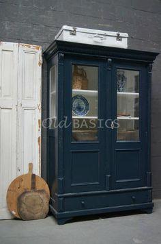 Vitrinekast 10147 - Prachtige brocante vitrinekast met opvallend mooie koof. De kast is sierlijk afgewerkt en heeft een grijs-blauwe kleur. In de zijkanten van de kast zit ook glas, dit geeft een leuke doorkijk! Achter de deuren drie vaste legplanken, onderin een lade.