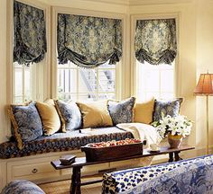 Shaded Bay:   Like the previous slide, this bay window features a built-in seat with storage. Yet here the homeowners opted for fabric shades rather than full draperies. This treatment may be more expensive than full draperies, yet are an attractive alternative to control light and privacy at the window level.