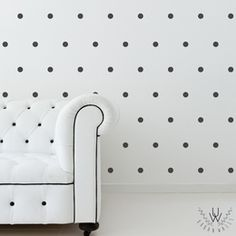 Matte black small polka dot wall stickers on a white wall behind a white couch. The decals are evenly spaced in a pattern.