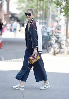 Olivia Palermo makes sneakers work appropriate by pairing them with a sporty bomber and a jumpsuit.