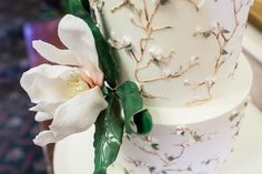 www.sylviaskitchen.co.uk Three tier Magnolia wedding cake.  Cake created for the Wedding Cake Showroom at the Annual Squires Kitchen Exhibition in Surrey.  Iced in pale lemon royal icing and finished with hand piped and hand painted fine magnolia branches, blooms and foliage.  Decorated with a full bloom large sugar wired magnolia and wired foliage.  Cake as shown would serve 120 finger portions.  Photographed by Clare from FitzGerald Photographic at The Grand Hotel, Eastbourne, East Sussex