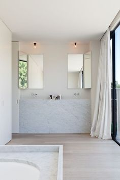White bathroom with concealable vanity mirrors. Photo by Tim Van de Velde.