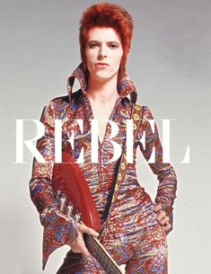 Bowie in reds patterned jumpsuit with large wing lapels. Will try to find out more about this jumpsuit.