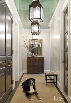 In the foyer, walls are covered in Schumacher's Imperial Trellis wallpaper, and the ceiling was lacquered by Luxe Painting in Benjamin Moore's Parsley Snips. A stool from Oly Studio provides seating, while the Hobe Sound black-lacquered lanterns by Oomph light the way.