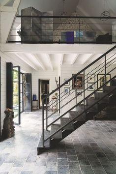 Pierres bleues pour le sol, poutres repeintes en blanc, escalier au style industriel : un salon métissé ! Plus de photos sur Côté Maison http://petitlien.fr/7exu