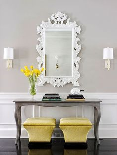 Traditional neutral gray entryway with white panel wainscoting. Gorgeous plush, slightly modern ottomans upholstered in a citron yellow velvet. Console table has an edgy vibe with a zinc painted finish. I would love to look at myself everyday in that fabulous intricate filigree white mirror.: