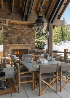 Enjoy the fresh air on this rustic cabin covered patio beautifully appointed with an oversized glass and iron lantern hung over a square concrete dining table surrounded by gray directors chairs place don gray floor tiles as a red stone fireplace keeps everyone warm and cozy.