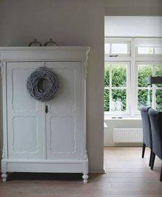 Wit geschilderde houten kast met grijze krans.