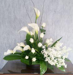 Diseño elegante de alcatraces $1,390.00 10 Alcatraces a desniveles en base tradicional, acompañados de rosas blancas y varas de orquídea dendrobium blancas. Es importante hacerle saber, que