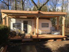 Caravan onder de veranda met zitruimte