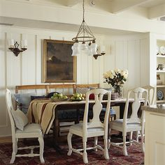 wood table with white chairs and upholstered bench.  Mona Hajj Interiors