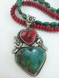 Argento Bello- Artist Amberlie Bandini. Turquoise and coral hearts set in sterling silver and embellished with handmade blossoms and leaves. Bought by collector Jennifer Johnson.
