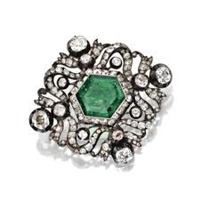 GOLD, SILVER, EMERALD AND DIAMOND BROOCH, CIRCA 1870-1890 Set in the center with a hexagonal-shaped emerald weighing approximately 10.40 carats, within an openwork frame of foliate and ribbon motif set with old mine and rose-cut diamonds weighing approximately 8.60 carats.