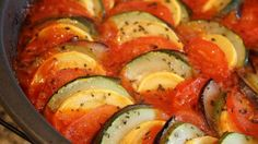 A beautiful deconstructed ratatouille is composed of sliced colorful vegetables arranged over a garlic-infused tomato sauce and baked. It's like the one in the animated movie.