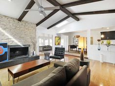 Nice modern living area. Love the exposed rafters.. Just put a big flat screen above the fireplace :)
