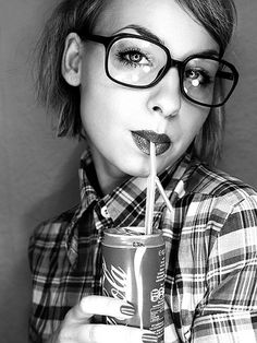 woman with short hair in large and thin black glasses, plaid button up shirt, sipping a coke with a straw -- #glasses #eyewear #style