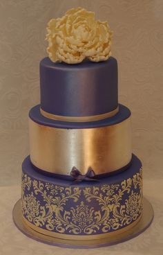 The bottom tier of this purple and gold cake is airbrush-lustered then has a stencilled and piped ivory royal icing damask pattern, middle tier is covered in pure edible silver leaf, and top tier is airbrush-lustered.